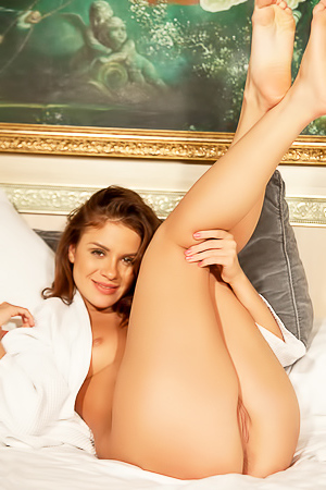 Luscious Leda is propped up in bed wearing a white robe